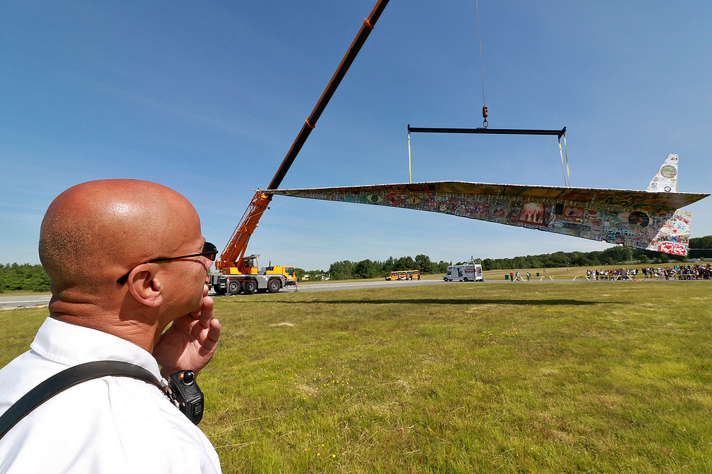 . Jerry Beck\'s Project Soar launched at the Fitchburg Municipal Airport on Tuesday morning, June 12, 2018. Watching the plane as it hangs from a crane is Fitchburg Fire Lt. Rich Liberatore.SENTINEL & ENTERPRISE/JOHN LOVE
