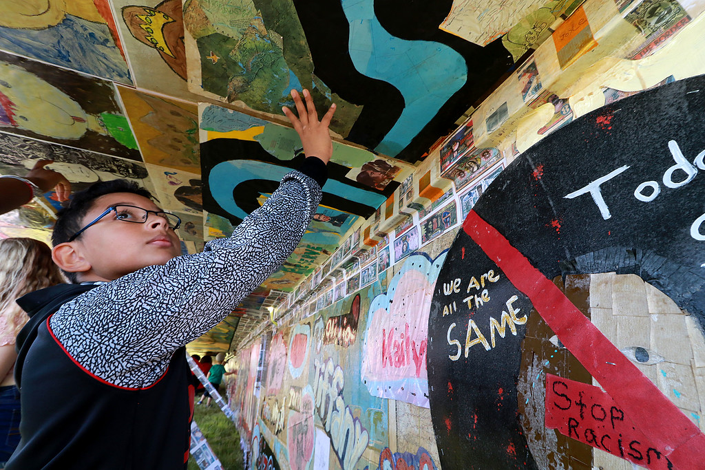 . Jerry Beck\'s Project Soar launched at the Fitchburg Municipal Airport on Tuesday morning, June 12, 2018. Getting a close up of the artwork on the plane is McKay Arts Academy student Rodrigo Deleon, 12. SENTINEL & ENTERPRISE/JOHN LOVE