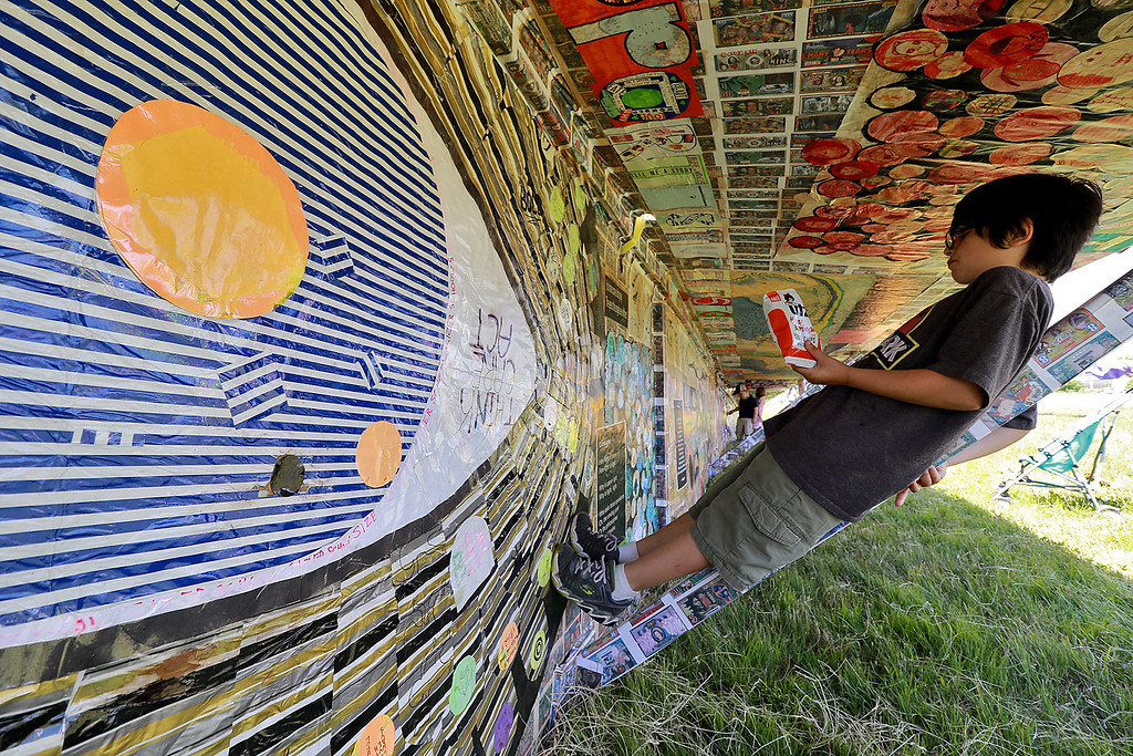 . Jerry Beck\'s Project Soar launched at the Fitchburg Municipal Airport on Tuesday morning, June 12, 2018. Felix Allen, 9, of Fitchburg relaxes as he look at the artwork on the plane during the event. SENTINEL & ENTERPRISE/JOHN LOVE