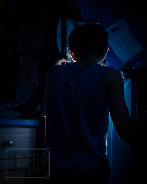 """Midnight Snack - Week 21 """"In the Fridge""""<br /> <br /> Seems like the kids are always sticking their heads in the fridge to see if anything has changed since the last time they did so.  For this photo I used a speedlight with a radio trigger (1/32 or 1/64 power I think) placed on the bottom shelf of the fridge and pointed directly at my oldest son standing at the door."""