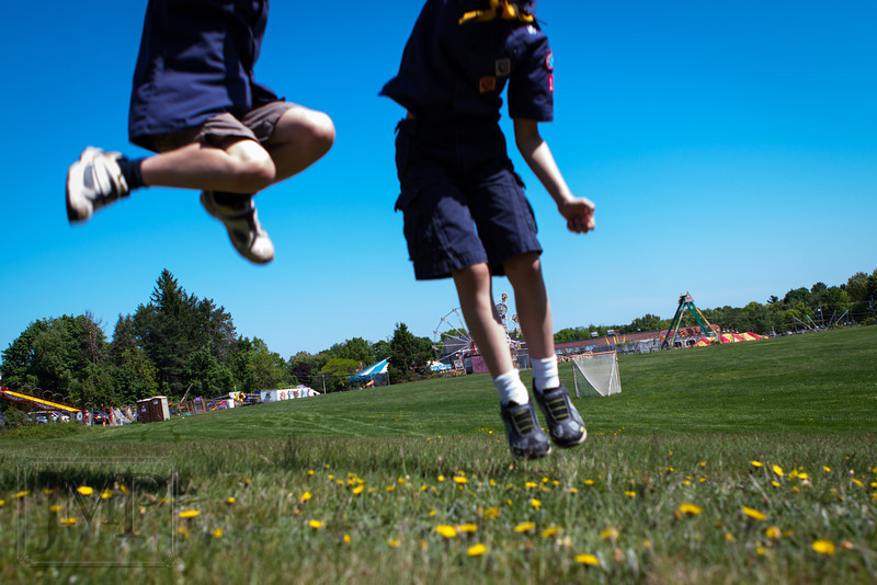 """Fair Flight - Week 20: """"Jump""""<br /> Two cub scouts jump in a field near a town fair.  I took this shot following the town parade in which these scouts had just marched.  There was a pretty big crowd of scouts and other people out of sight behind us, and one of them even sent me a """"making of"""" type photo with me laying on the grass taking this photo."""