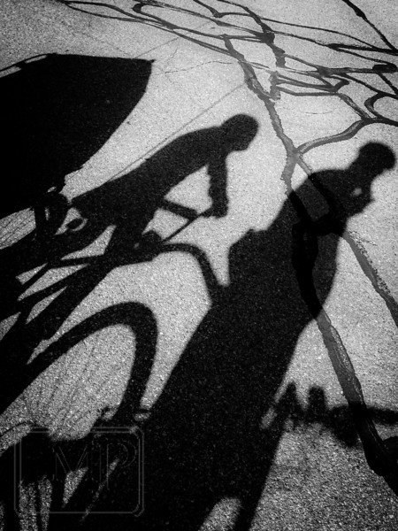 "Bicycle Train - Week 18: ""Shadows"" - I had the family out for a ride with the bicycle train in tow behind me. We had stopped at the end of the trail and I noticed our shadows mingling with the black tar patches on the pavement, so I took a few quick shots to add to my list of options for this week's entry.  I made a few adjustments to really emphasize the darkness and contrast and I'm pretty happy with the way this came out."