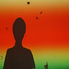 "Against a Red Sky - Week 36: ""Sunset""<br /> <br /> I happened upon this artificial sunset quite accidentally at the Boston Children's Museum this week.  This silhouette is really the shadow of my son as he waits for an animated butterfly to land on his shadow on the projection screen.  To our eyes the screen appeared to be all white save for the fluttering creatures, but under the speed of the camera we revealed a colorful refresh of the projection.  When I saw this I immediately thought of an ocean sunset and knew I had my photo for this week's assignment."