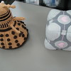 Knit Dalek vs. Weighted Companion Cube<br /> <br /> The wife of one of my co-workers is unbelievably cool. I had suspected it before, but confirmation came today when I spotted this knitted Dalek on his desk at work. That's just full of awesome.<br /> <br /> It was his idea to pit it against my Valve-store-bought Weighted Companion Cube. No contest there.