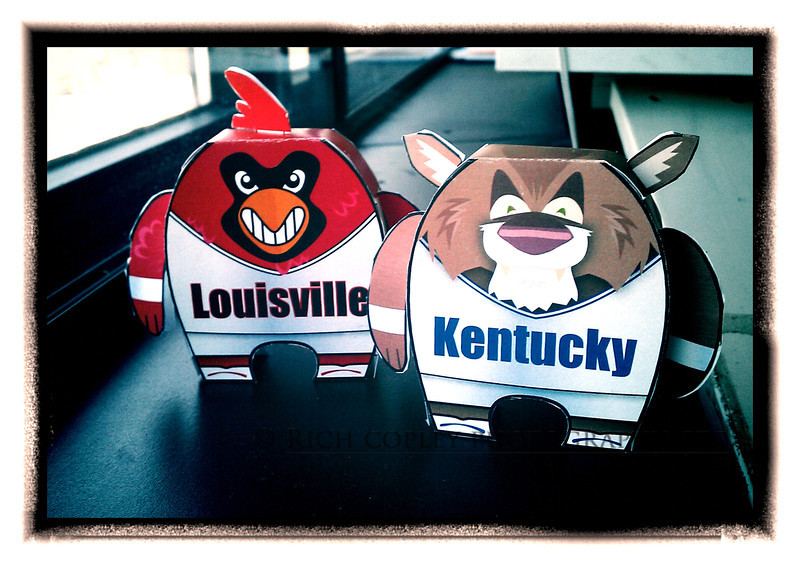 "March 29, 2012 - I was not planning to do two straight days of Uncle Herald products. These are craft paper toy figures of the University of Louisville Cardinal and University of Kentucky Wildcat designed by staff artist Chris Ware. He says these sorts of figures are very big in Japan these days. Anyway, we have downloadable versions of them at LexGo - <a href=""http://bit.ly/H1ed9n"">http://bit.ly/H1ed9n</a> - that you can print and make. When I saw them online, I thought they looked real cool, but we didn't have anything showing how the finished product should look. So, I grabbed Chris' models and took a quick shot using some window light. Now, tomorrow, I promise: real camera and no Herald-Leader products. But I really did think these were cool. (105/366)"