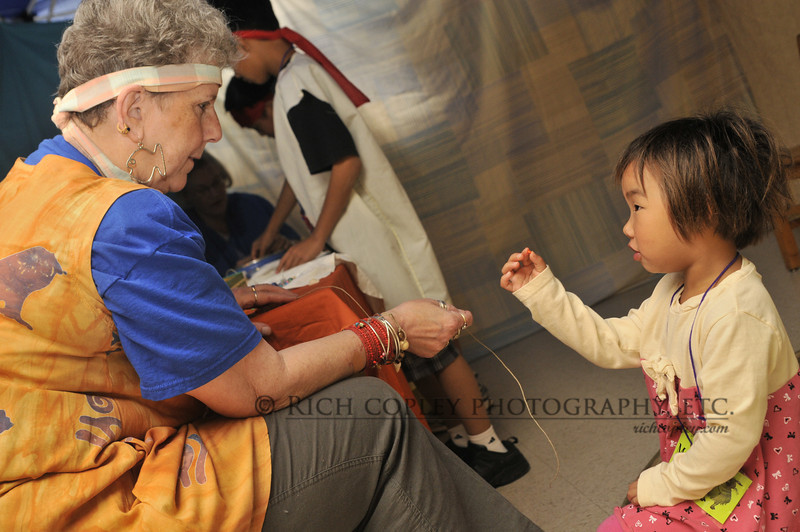 June 5, 2012 - I have mentioned my friend Mary Lois before. This is her, helping a little girl make a necklace at Maxwell Street's Nazareth-themed VBS. (173/366)