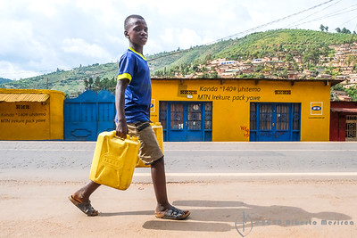 a kid carrying water to his family, Kigali, Rwanda