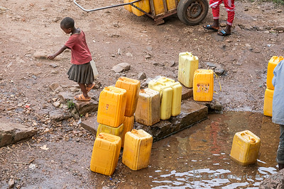 a kid has just filled up her jerry can