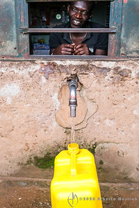 a water merchant at his stand dispensing water