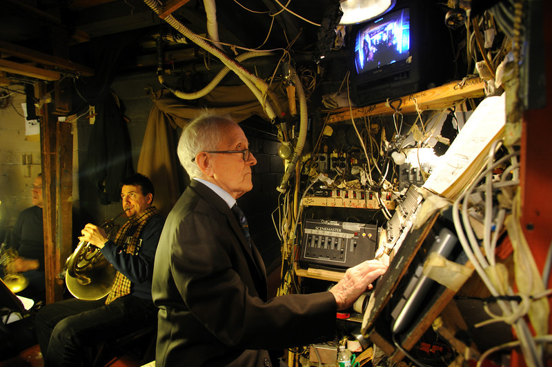 Below the stage, in the orchestra pit, Maestro Anthony (Tony) Amato at the lighting board and supertitle machine<br /> Amato Opera Theatre, New York City<br /> © Laura Razzano