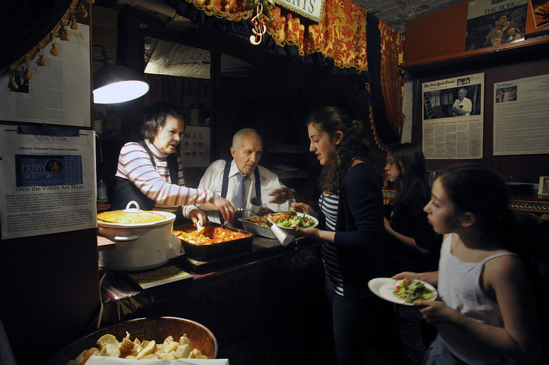 Amato Opera Theatre, 319 Bowery, NYC.<br /> Last Season 2009<br /> © Laura Razzano<br /> <br /> (L-R) Lorraine Davidson, singer and Maestro Anthony Amato serve dinner to the volunteers who helped to dismantle sets of La Boheme and to built the stage for to the Marriage of Figaro.