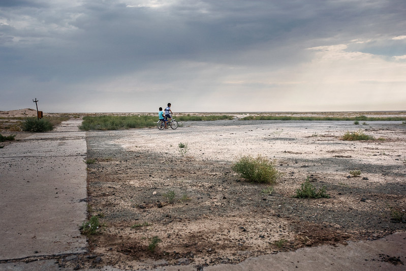 Uzbekistan – Kubla Ustyurt (autonomous republic of Karakalpakstan) - August 2015 – Children play on bikes on the streets of Kubla Ustyurt. The village gardens are parched, the kindergarten closed, there is only limited water in the pipes.