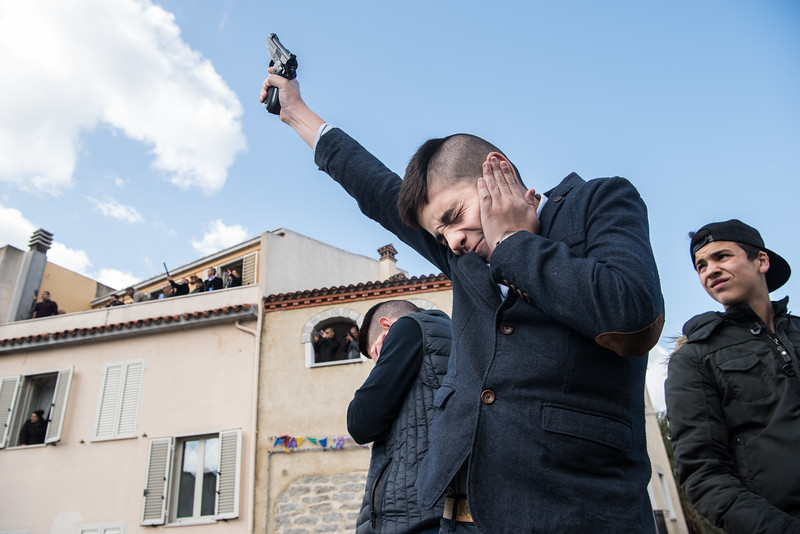 """April 1, 2018  A young man shoots in the air during the religious celebration of """"S'incontru"""", an ancient rite held on Easter's Sunday in Oliena, Italy. Gunmen shoot in the air to announce Jesus's resurrection and scare away the evil spirits that might interfere with this important day."""