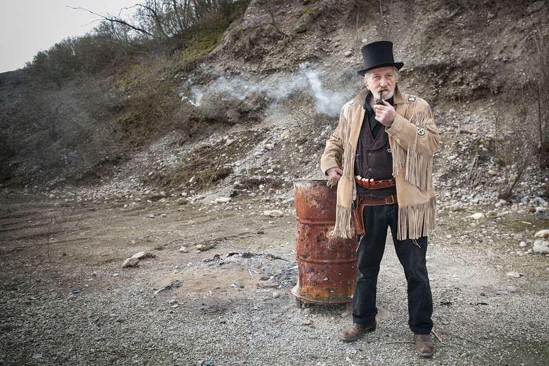 """March 25, 2018   Raffaele (64), known as """"Pit Karson"""", smokes during a break of a Cowboy Action Shooting competition in Verano Brianza, Italy. Participants wear old west style dresses and challenge themselves in a variety of shooting scenarios using old-fashioned firearms as single action revolvers, pistol caliber lever action rifles, and shotguns, and competes in time and accuracy of their shots."""