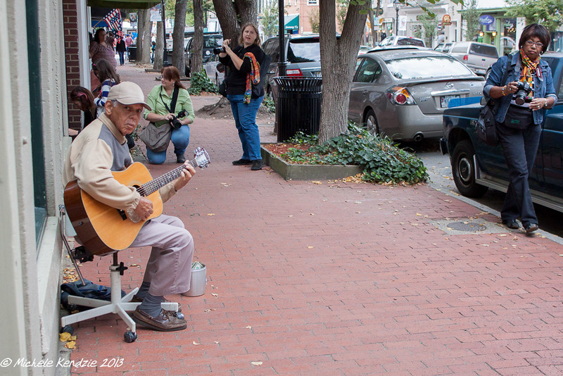street musician being shot by many photographers