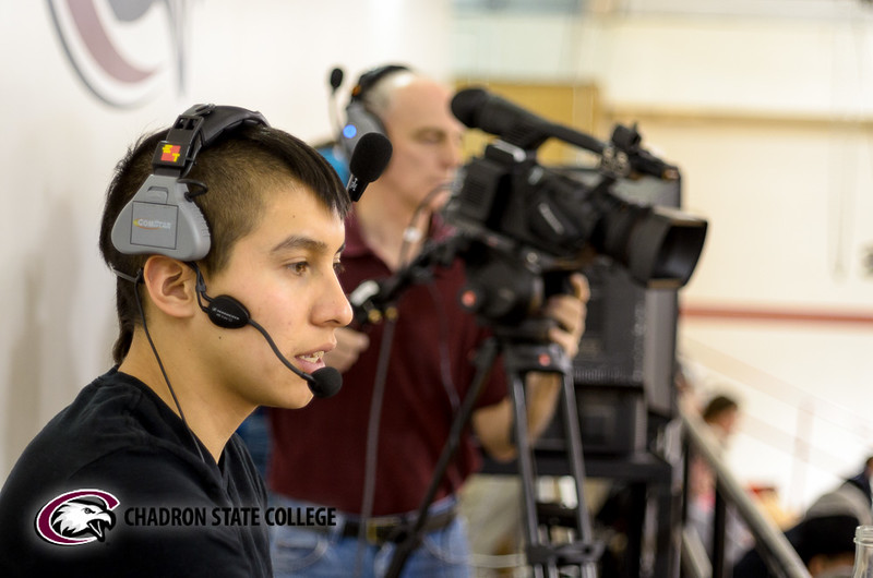 Will McLaughlin provides play-by-play commentary during a basketball game. Dewayne Gimeson, publications specialist, operates a camera in the background. (Photo by Daniel Binkard/Chadron State College)