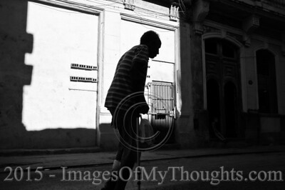 A man walks down a street in Havana, Cuba. Cubans spend much time at their doorways and many activities take place on the doorstep and street, creating a sense of community with their neighbors.
