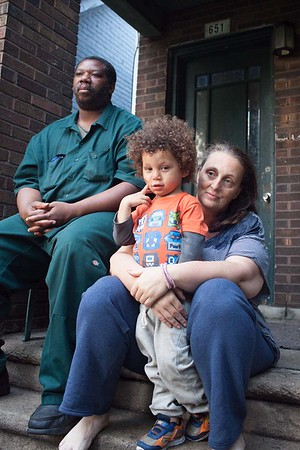 Isaac, Cindy and Isaiah (Issaac Jr.) on their porch. Issaac grew up in the suburbs. Him and Cindy have been moving from place to place in Delray for about 20 years. They will be moving to River Rouge in a month. She wanted to stay in Southwest; she loves Southwest. It is very diverse. But they couldn't find a house they could afford with the money MDOT is giving them.