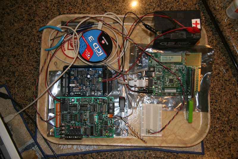Tray of parts becomes my development platform.  Shown here are the Explorer 16 board (right), RS-232/RS-485 converter (center left), temperature sensor (white bread board) and AT444A board (bottom left).  The RE Smith AT444A provides 4 DIs, 4 Analog Ins and 4 relays.