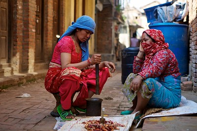 Pounding chillies outside a house in Bungamati.