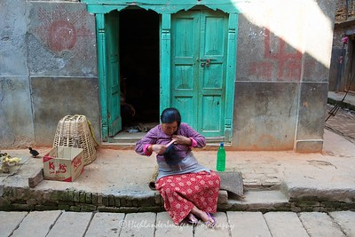 Local lady combs her hair on the roadside in Bungamati.