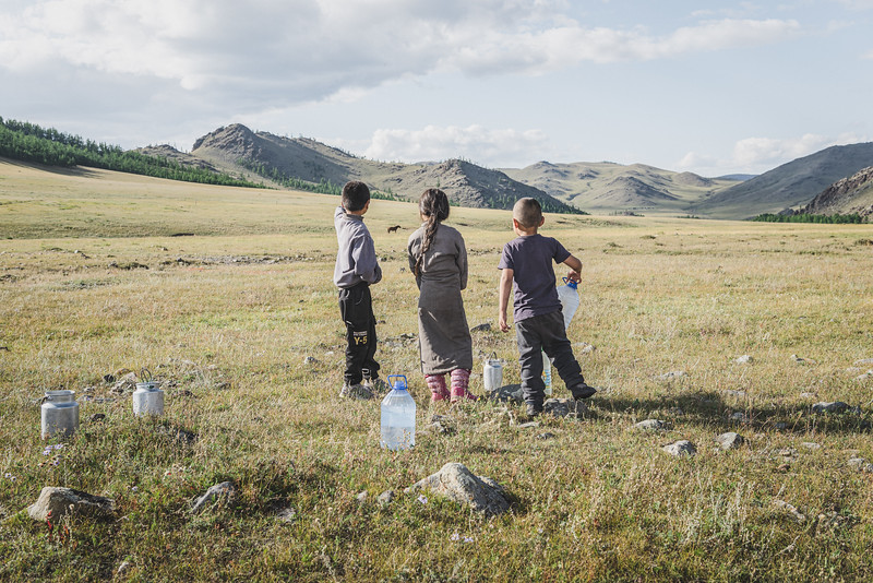 Mongolia, Gobi, 2019. Children carry water to their father's ger. The main river providing surface water to the southern Gobi – the Undai River – has been diverted by the Oyu Tolgoi copper and gold mining. Local herders have expressed concerns that the promise of creating new water sources will never be realised.