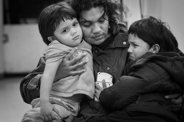 Angela DeClue comforts her sons Sean,2, and Alexander, 5.   The  homeless family spend their days at the Family and Adult Service Center in Seattle. At 8:20 each evening the family must board a city bus for a 40 minute ride to a church which provides them a place to sleep for the night. At 6:20 each morning the family is awakened and by 6:40 they are on a bus heading back to the FASC facility downtown. From there the older children depart on another one hour bus ride to school while their parents deal with the small children and the sometimes daunting bureaucracy faced by the homeless.