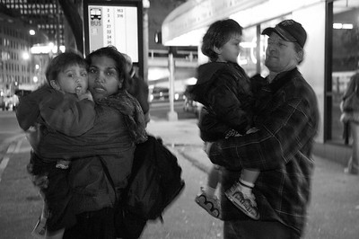 Angela and Leonard DeClue, and their children wait at a downtown bus stop during their search for shelter housing.