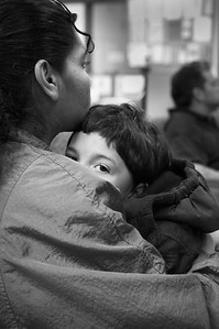 Alexander DeClue, 5, recovering from a long day of traversing Seattle by bus and the added trama of half a dozen shots and vacinations, rests in his mother's arms at the Family and Adult Service Center in downtown Seattle.    The  homeless family spend their days at the Family and Adult Service Center in Seattle. At 8:20 each evening the family must board a city bus for a 40 minute ride to a church which provides them a place to sleep for the night. At 6:20 each morning the family is awakened and by 6:40 they are on a bus heading back to the FASC facility downtown. From there the older children depart on another one hour bus ride to school while their parents deal with the small children and the sometimes daunting bureaucracy faced by the homeless.