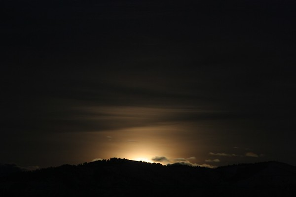 As the moon rises up to the horizon it lights up the sky with a curious glow.