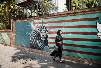 August 11, 2017 – Teheran, Iran. An Iranian woman walks in front of an anti-American wall painted on the wall of the ex US embassy in Tehran. [The famous graffiti in front of the old US Embassy, occupied by a group of students from November 4, 1979 to January 20, 1981, holding 52 officials hostage.] © Simone Tramonte