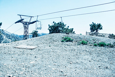 A discarded plywood sheet provides a compositional anchor to the ski tower disappearing behind the ridge. Small ground bushes echo the lines of the cables above. The crushed rock base of this lookout lays in stark contrast to the open sky above.