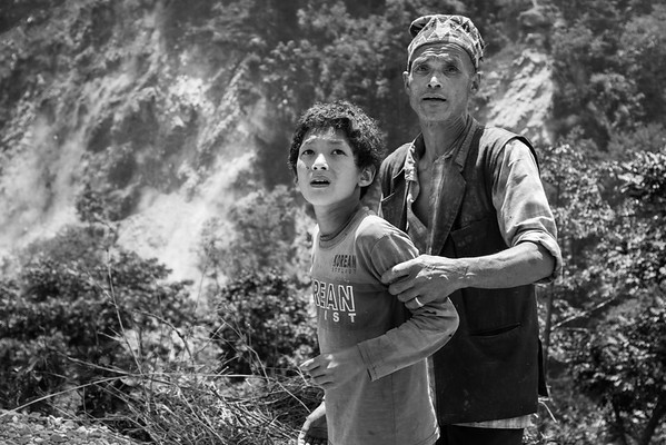 Father protecting his son as they are looking at the incoming landslides.