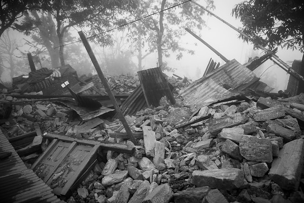 Destroyed remains of a house in the morning mist in the mountains of Gorkha region, after the first earthquake.