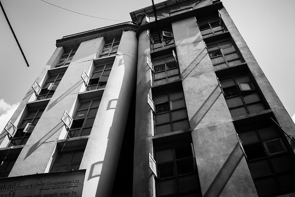 A building leans on the other in Kathmandu. People are still living inside both of them.
