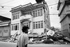 A man looks at a three story house that collapsed on its first floor in Kathmandu.