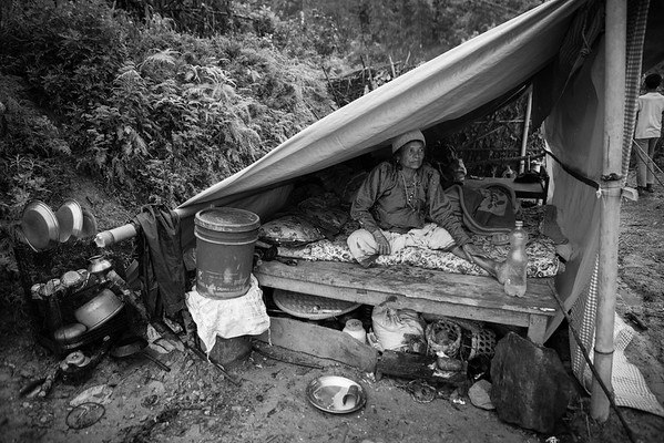 A villager has set up a tent outside her house. Even if their houses still stand, the structures are fragile and villagers fear for aftershocks that could demolish what remains. Many have set up tents next to their houses where they now live and sleep.