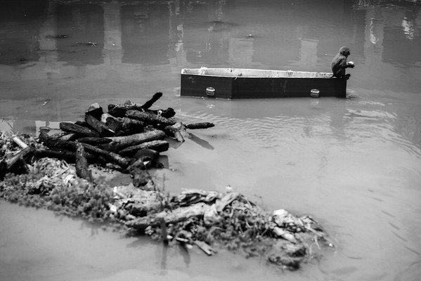 A monkey sits on a coffin, going down the Bagmati river in Pashupatinath Temple where cremations of bodies are taking place.