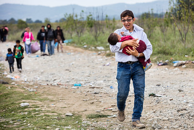 An Afghan man walks in the fields towards the transit camp of Gevgelija with his child in his arms and his family behind. Gevgelija, Macedonia. October 2015. ----------- Un homme afghan marche dans les champs en direction du camps de transit de Gevgelija avec son enfant dans les bras et sa famille derrière. Gevgelija, Macédoine. Octobre 2015.