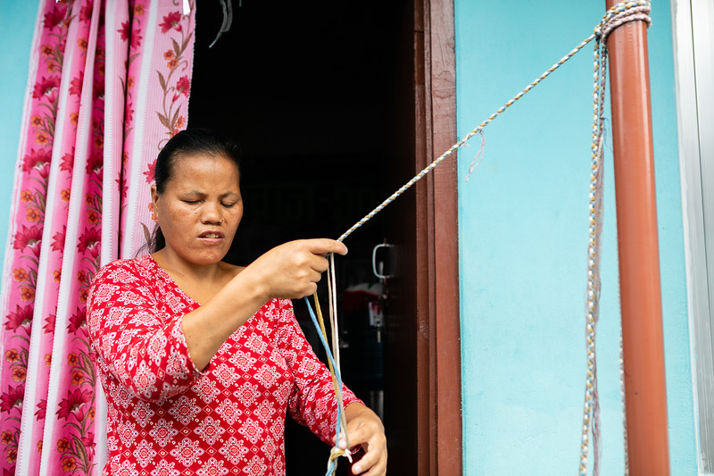 Phul Kumari has been working with WSDO for the past 6 years as a braid maker. She lives with her husband in a community which helps blind people like them, and she works from her home most of the time. This job allows her to support her family as well as take care of Prasun, her son who is sighted.