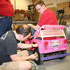 Kevin Fusselman installs a support spring on the hand brake while Ben Hutcheson ensures it won't interfere with driving.