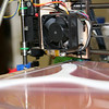 The extruder of the RepRap Mendel 3D printer lays down a layer of ABS filament.