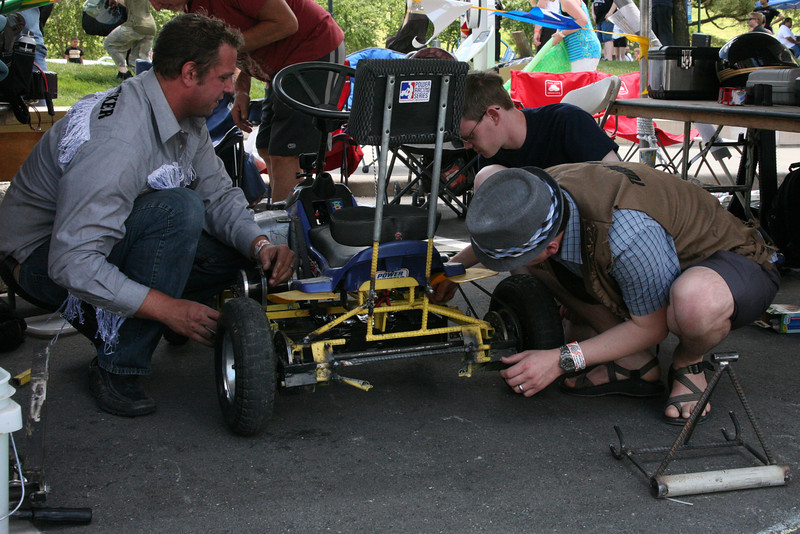 With the battery pack rebuilt, Kyle Deloske (L), Ben Hutcheson (C), and Kevin Fusselman (R) install it in the #2 car.