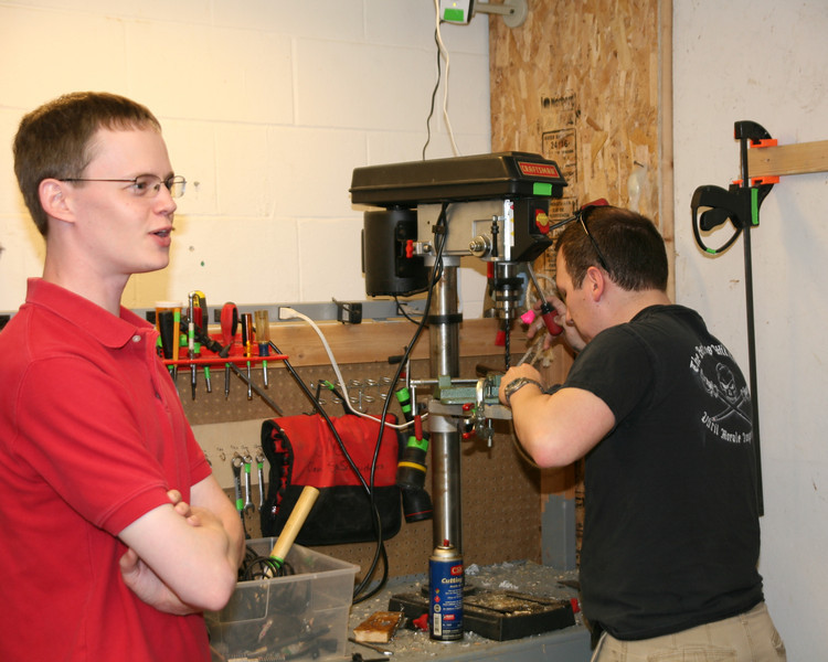 Ben Hutcheson (L) discusses the operation of the Jeep while Kevin Fusselman (R) drills the handle of the brake.