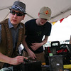 Using basic soldering tools and a meter, Kevin Fusselman (L) and Ben Hutcheson (R) repair the #2 battery pack.