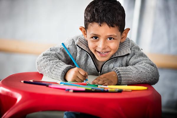 A young refugee enjoys his time, drawing and playing in the UNICEF tent before going back on the road from Gevgelija transit camp.<br /> Gevgelija, Macedonia. October 2015.<br /> -----------<br /> Un jeune réfugié profite d'un moment de jeu et de dessin dans la tente UNICEF avant de reprendre son périple depuis le camp de transit de Gevgelija.<br /> Gevgelija, Macédoine. Octobre 2015.