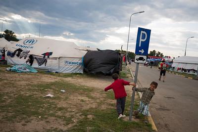 Two young refugees play around a camp set up in a gas station near the Macedonian border in Greece. Polykastro, Greece. May 2016 ----------- Deux jeunes garçons jouent au milieu d'un camp de réfugiés établi dans une station-service près de la frontière macédonienne en Grèce. Polykastro, Grèce. Mai 2016