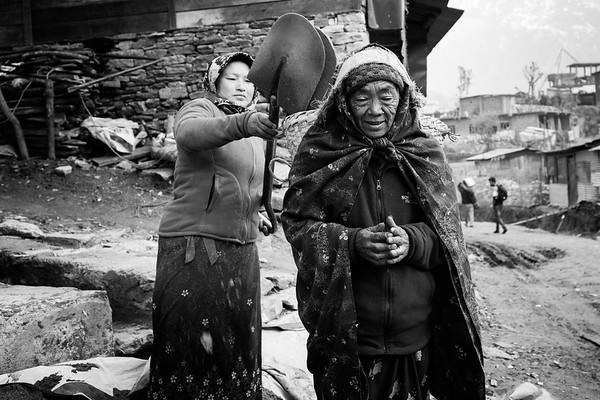 A woman loads with heavy stones the basket on the back of an old lady, working on a construction site in Barpak, village located at the epicenter of the 2015 earthquake.<br /> Barpak, Nepal. March 2017<br /> -----------<br /> Une femme devant l'abri temporaire où elle vit encore, deux ans après les tremblements de terre au Népal.<br /> Barpak, Népal. Mars 2017