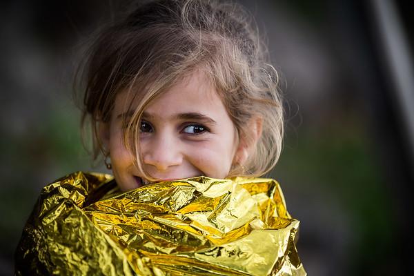 A refugee girl, still wrapped in an emergency blanket, smiles on Lesvos island shores as she just got off the boat crossing the Aegean sea from Turkey.<br /> Lesvos Island, Greece. October 2015.<br /> -----------<br /> Encore enveloppée de sa couverture d'urgence, une jeune fille réfugiée sourit alors qu'elle vient de débarquer sur les plages de Lesbos après la traversée de la mer Égée.<br /> Ile de Lesbos, Grèce. Octobre 2015.