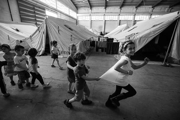 A group of children play around a refugee camp set up in a discarded hangar in Northern Greece.<br /> Thessaloniki, Greece. May 2016<br /> -----------<br /> Un group d'enfants s'amusent dans un camp de réfugiés installé dans un hangar abandonné dans le nord de la Grèce.<br /> Thessaloniki, Grèce. Mai 2016